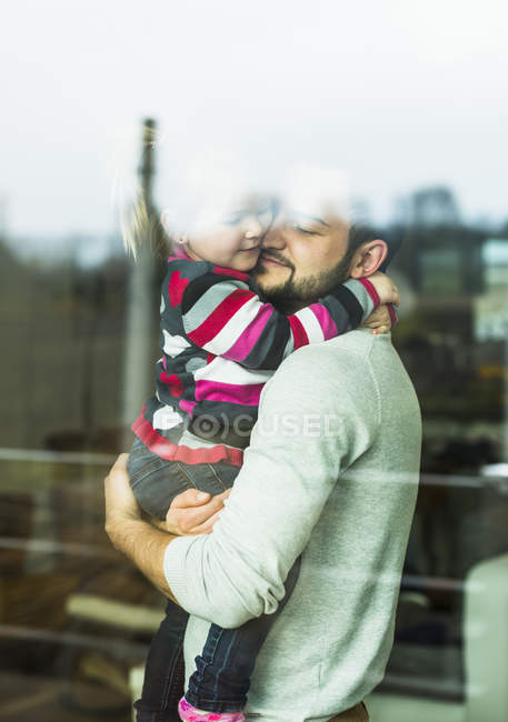 Father and daughter hugging behind windowpane — Stock Photo