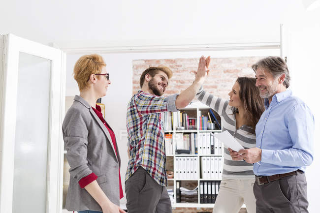 Happy business people giving high five in office — Stock Photo