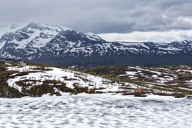 Norwegen, Nordland, gefrorener See und einsames Ferienhaus — Stockfoto