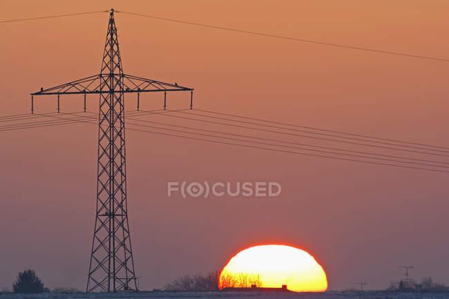 Германия, закат, кроме электроэнергии пилон — стоковое фото