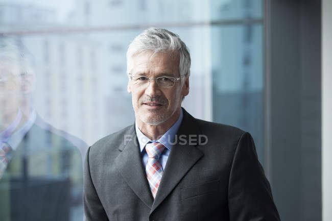 Businessman standing at window, portrait — Stock Photo