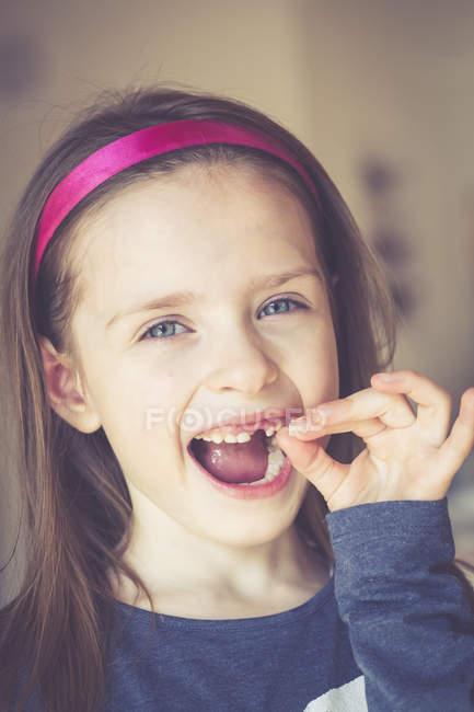Ritratto di bambina sorridente con uno spazio tra i denti che tiene in mano il dente del latte — Foto stock