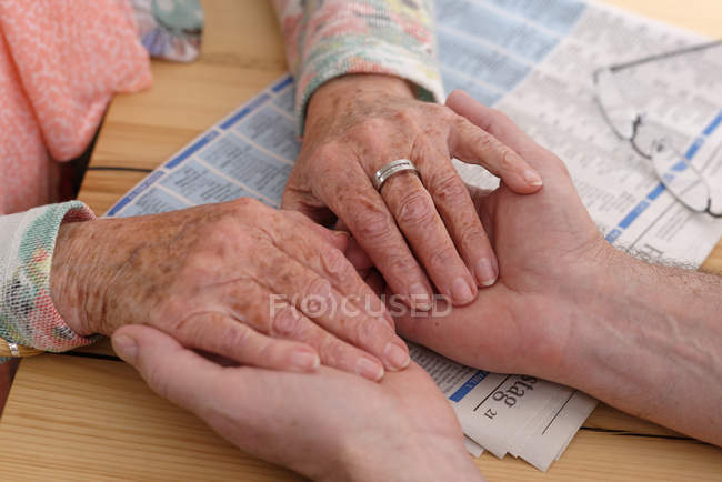 Hands of senior woman holding man's hands — Stock Photo
