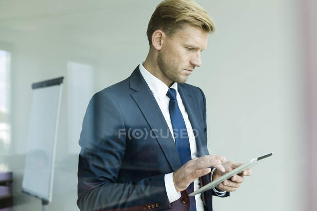 Businessman holding digital tablet, looking down — Stock Photo