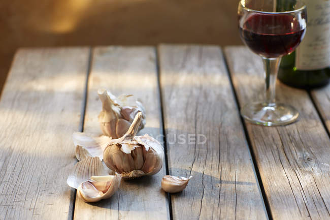 Garlic cloves and glass of red wine — Stock Photo