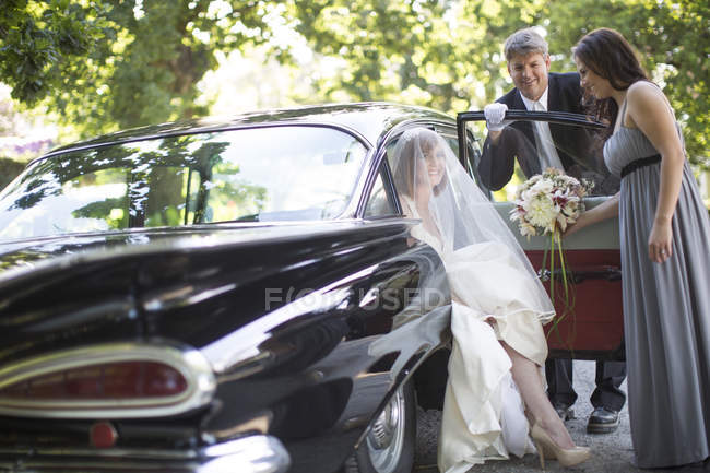 Bride getting out of car before wedding with driver and maid of honour — Stock Photo