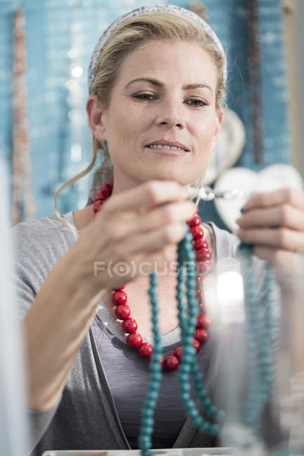 Femme inspectant un collier de perles — Photo de stock