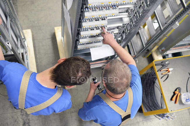 Two workers in a switchboard construction factory — Stock Photo