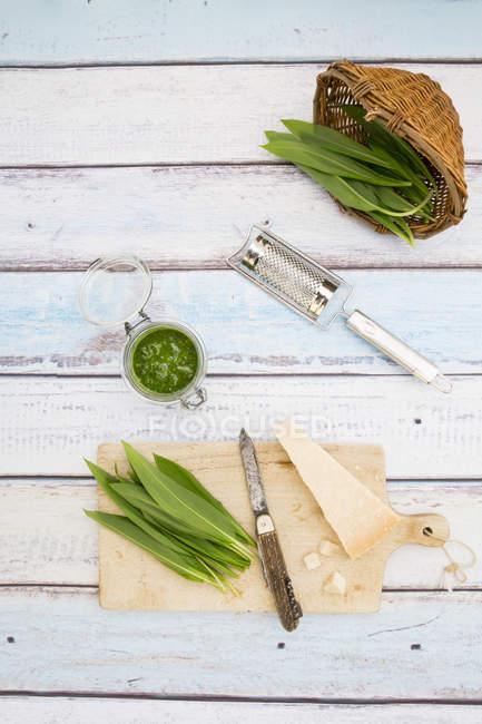 Vidrio de ramson orgánica pesto, hojas frescas de ramson, rallador de queso, cuchillo y parmesano en madera vista de superficie, superior - foto de stock