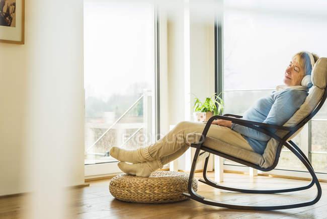 Donna anziana a casa rilassante con le cuffie — Foto stock