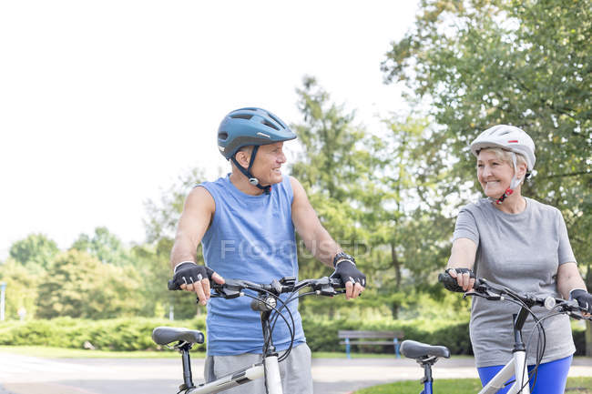 Happy senior couple with cycling helmets and bicycles — Stock Photo