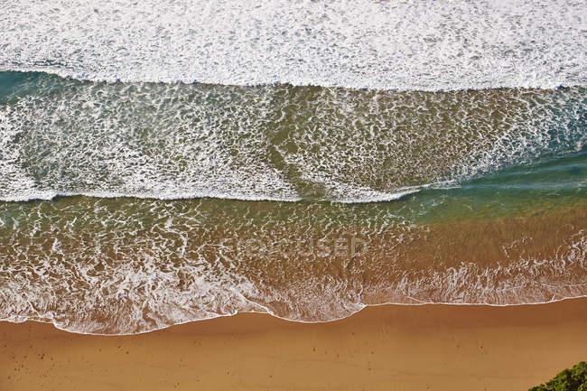 Vagues à venir sur la plage de sable fin — Photo de stock