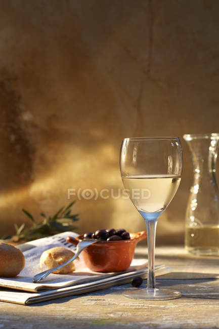 Still life with glass of white wine, black olives and newspaper — Stock Photo