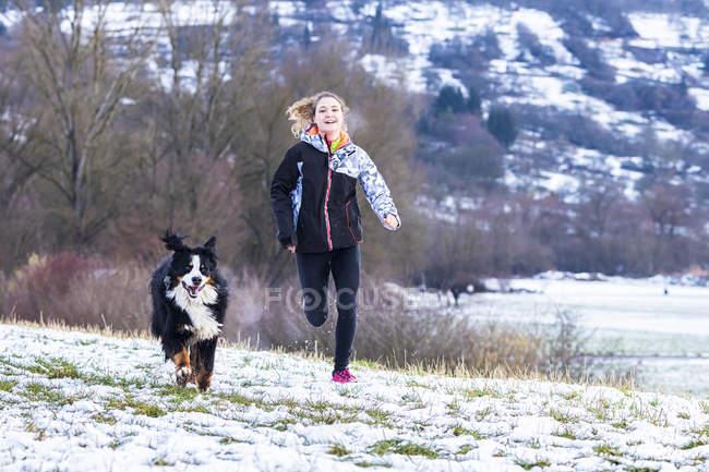 Молодая женщина, бег с ее Святой Бернард на заснеженной поляне — стоковое фото