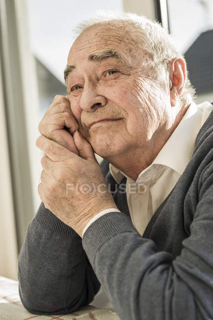 Portrait of senior man sitting at the window — Stock Photo