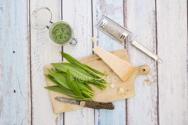 Vidrio de ramson orgánica pesto, hojas frescas de ramson, rallador de queso, cuchillo y parmesano sobre tablero de madera - foto de stock