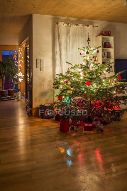 Árbol de Navidad decorado en una sala de estar - foto de stock