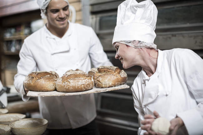 Panaderos que huele a pan fresco del horno - foto de stock