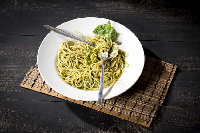 Plat de spaghettis au pesto Genovese servi sur plaque blanche, vue — Photo de stock