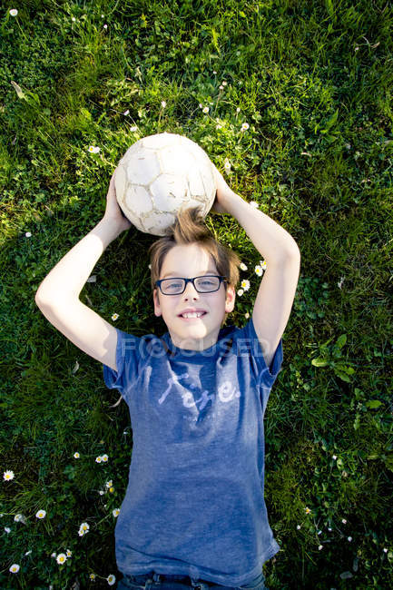 Портрет хлопчик, лежачи на луг з футбольним м'ячем — стокове фото