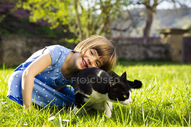 Portrait of smiling little girl with cat on a meadow — Stock Photo