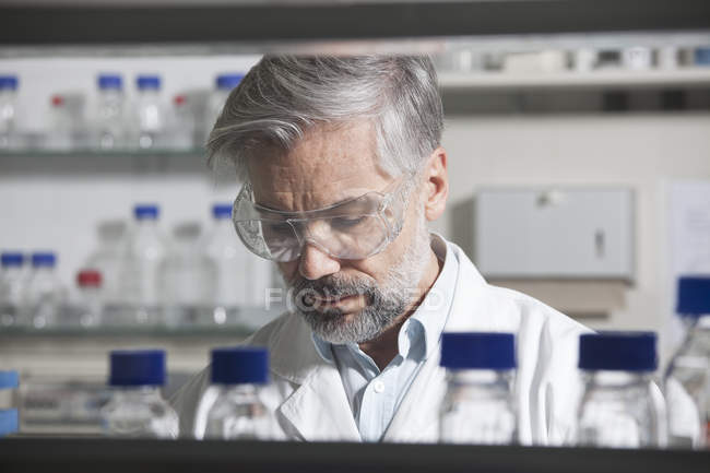 Scientist in laboratorywearing safety glasses — Stock Photo