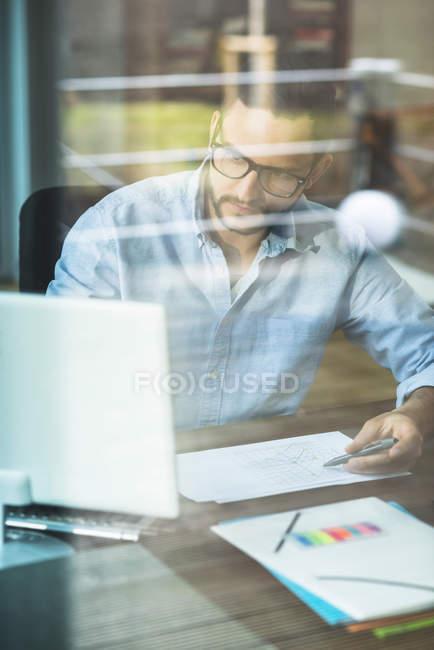 Junger Mann hinter Fensterscheibe arbeitet am Computer — Stockfoto