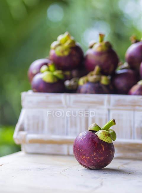 Свежий Мангостин с коробкой мангостинов на садовом столе — стоковое фото