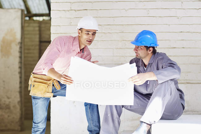 Construction worker and foreman discussing building plan — Stock Photo