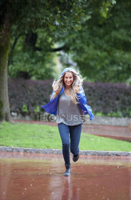 Усміхаючись Дівчинка-підліток працює під дощем — стокове фото