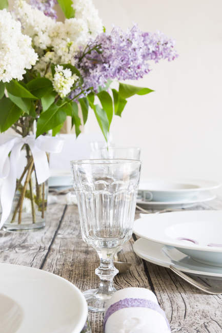 Wooden laid table with white and violet lilac — Stock Photo