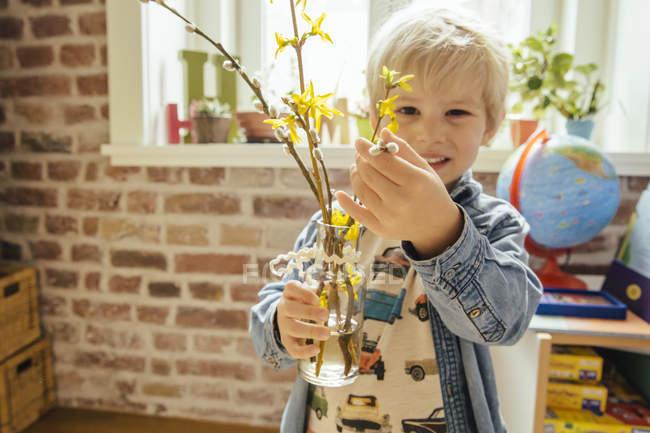 Ragazzino in possesso di vaso con catkin salice e forsythia — Foto stock
