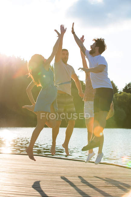 Four friends high fiving at a lake in backlight — Stock Photo