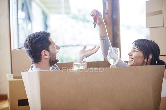 Casa móvil pareja sentado en una caja con llave y copas de vino - foto de stock