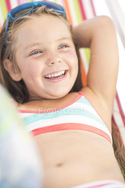 Ragazza felice sulla spiaggia rilassante su una sedia a sdraio — Foto stock