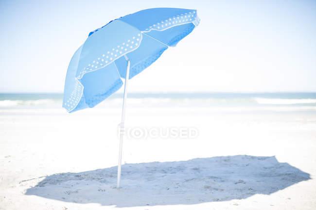 Голубой зонтик на белом песчаном пляже, морской пейзаж — стоковое фото