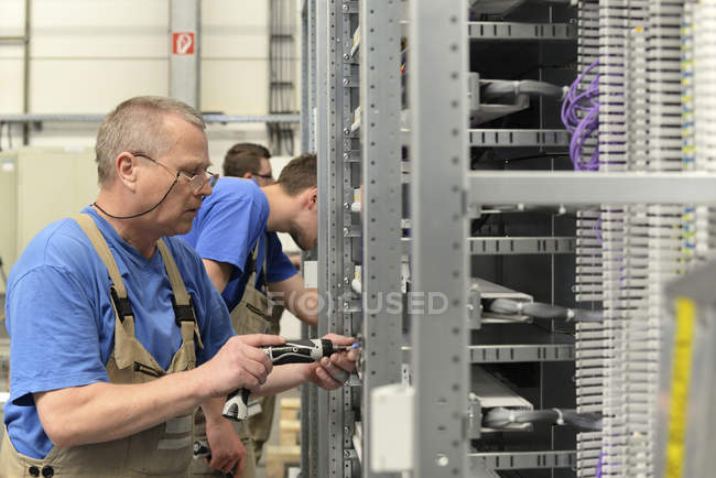 Working men on switchboard construction factory — Stock Photo