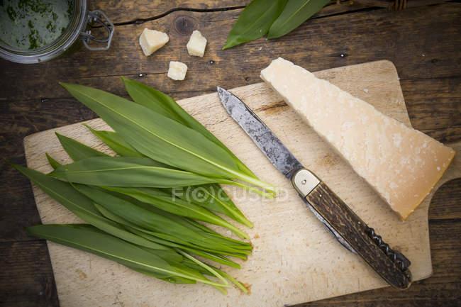 Zutaten für die Zubereitung von Bärlauch Pesto, Blätter und Käse auf Holzbrett mit Messer — Stockfoto