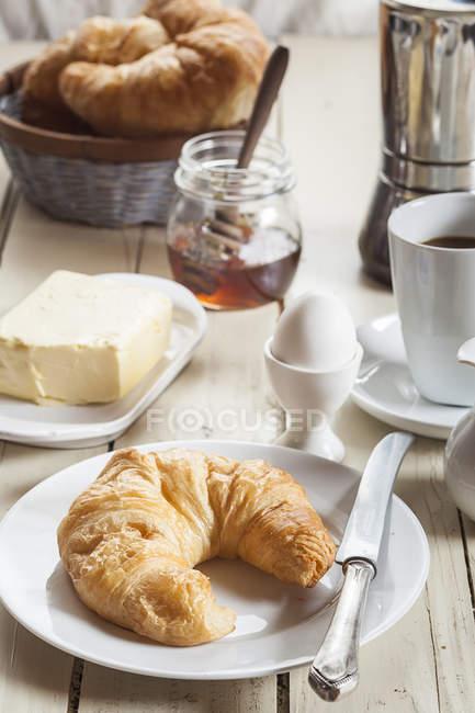 Frühstück mit Croissant, Ei, Kaffee, Honig und butter — Stockfoto