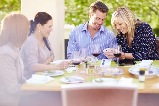 Frau zeigt Freunden am Esstisch Handy — Stockfoto