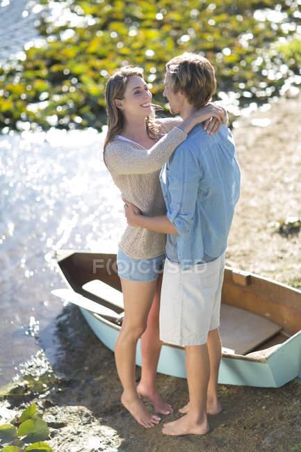 Молода пара, підтримуючи в озера — стокове фото