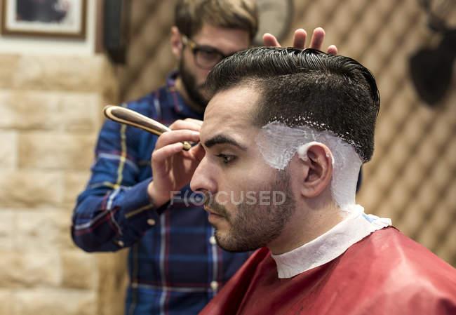 Parrucchiere rasatura capelli di giovane uomo in un barbiere — Foto stock