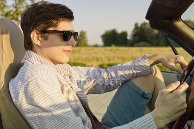 Adolescente con occhiali da sole guardando il suo smartphone in una macchina convertibile — Foto stock