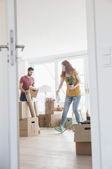 Young couple in new flat unpacking cardboard boxes — Stock Photo