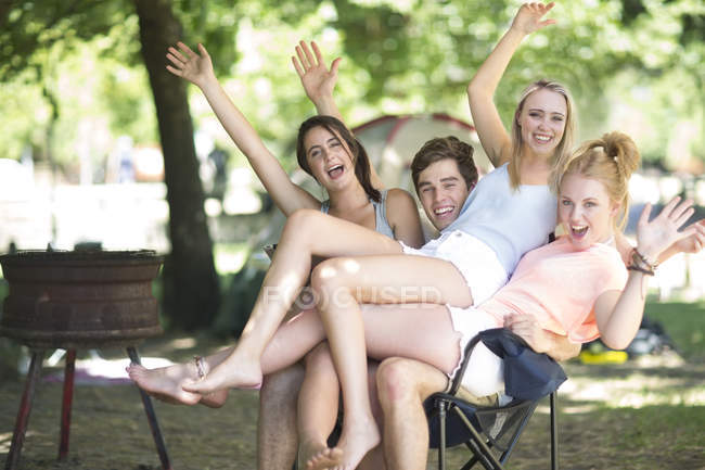 Playful friends on holiday sitting on the same chair — Stock Photo