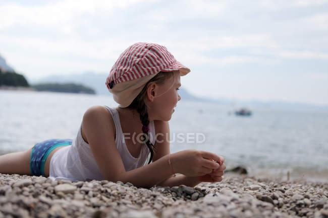 Дівчина з кришкою, лежачи на кам'янисті пляжі — стокове фото