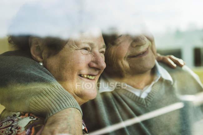Glückliches Senioren-Paar blickt durch Fenster — Stockfoto