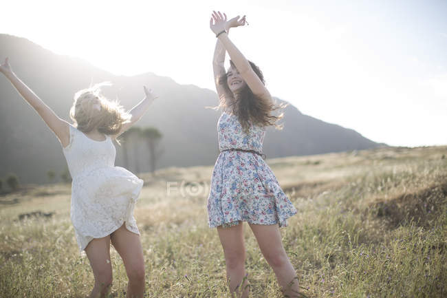 Female friends jumping of joy in field — Stock Photo