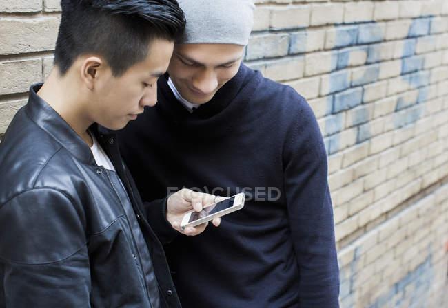 Молодая гей-пара, стоящая на улице и смотрящая на смартфон — стоковое фото