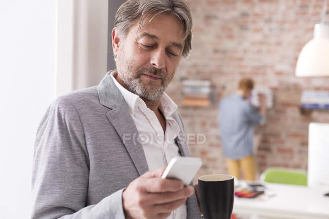 Empresário com telefone celular e café no escritório — Fotografia de Stock